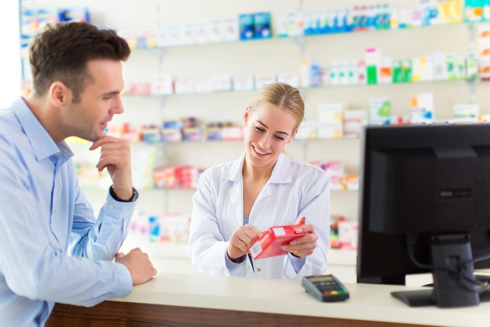 foto de uma mulher atendendo um homem, representando como abrir uma drogaria