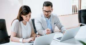 Foto de um casal conversando e mexendo no computador, representando como empreender em niterói
