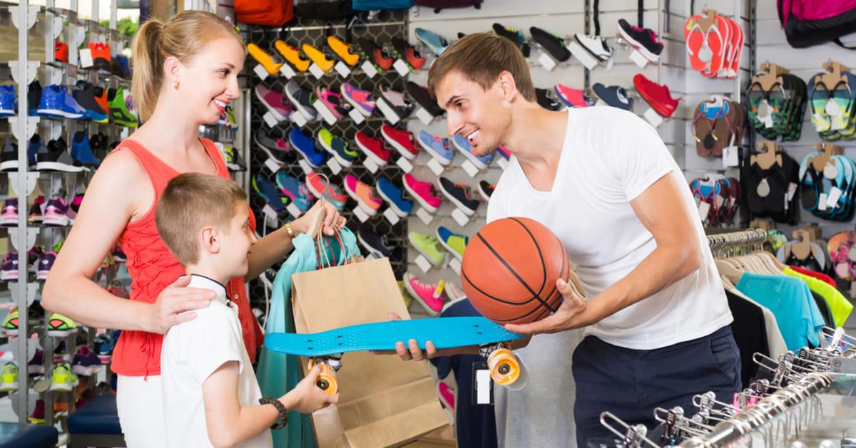 foto de um vendedor entregando uma bola de basquete para uma criança, representando como abrir uma loja de artigos esportivos