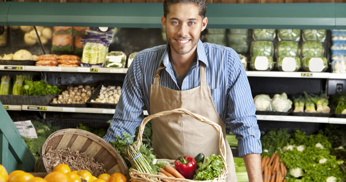 foto de um homem em frente a alguns legumes, representando como abrir uma loja de produtos naturais
