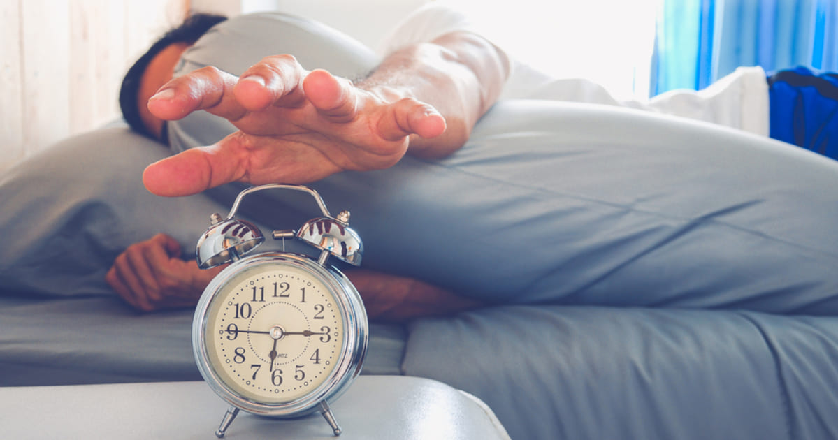 foto de um homem apertando um relógio, representando as dicas para acordar melhor