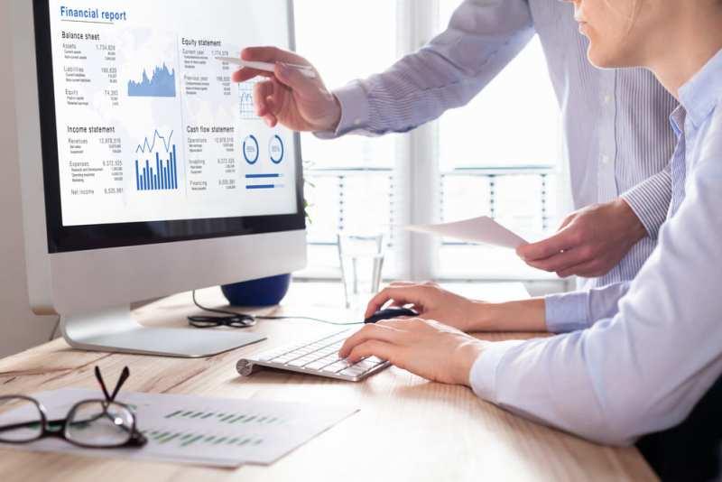 Foto de duas pessoas analisando um computador, representando como conseguir investidores
