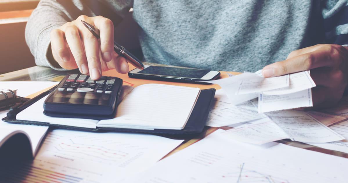 Foto de uma pessoa calculando as notas fiscais, representando a NFe 4.0
