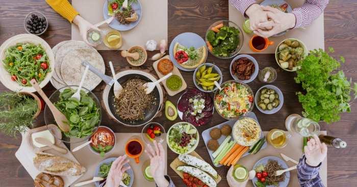 foto de uma mesa com comidas, vegetais e outros pratos, representando como abrir um restaurante vegetariano