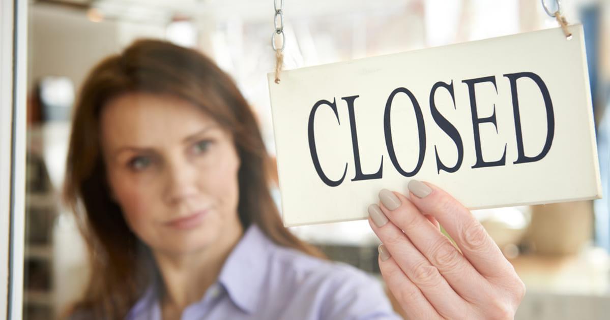 """Foto de uma mulher segurando uma placa de loja escrita """"fechado"""", representando as empresas fechadas"""