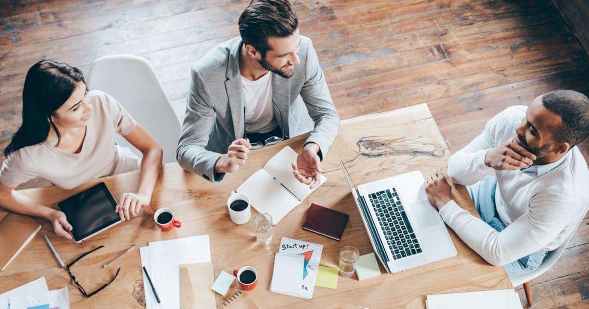 foto de três pessoas sentadas a uma mesa, representando a importância da gestão de talentos