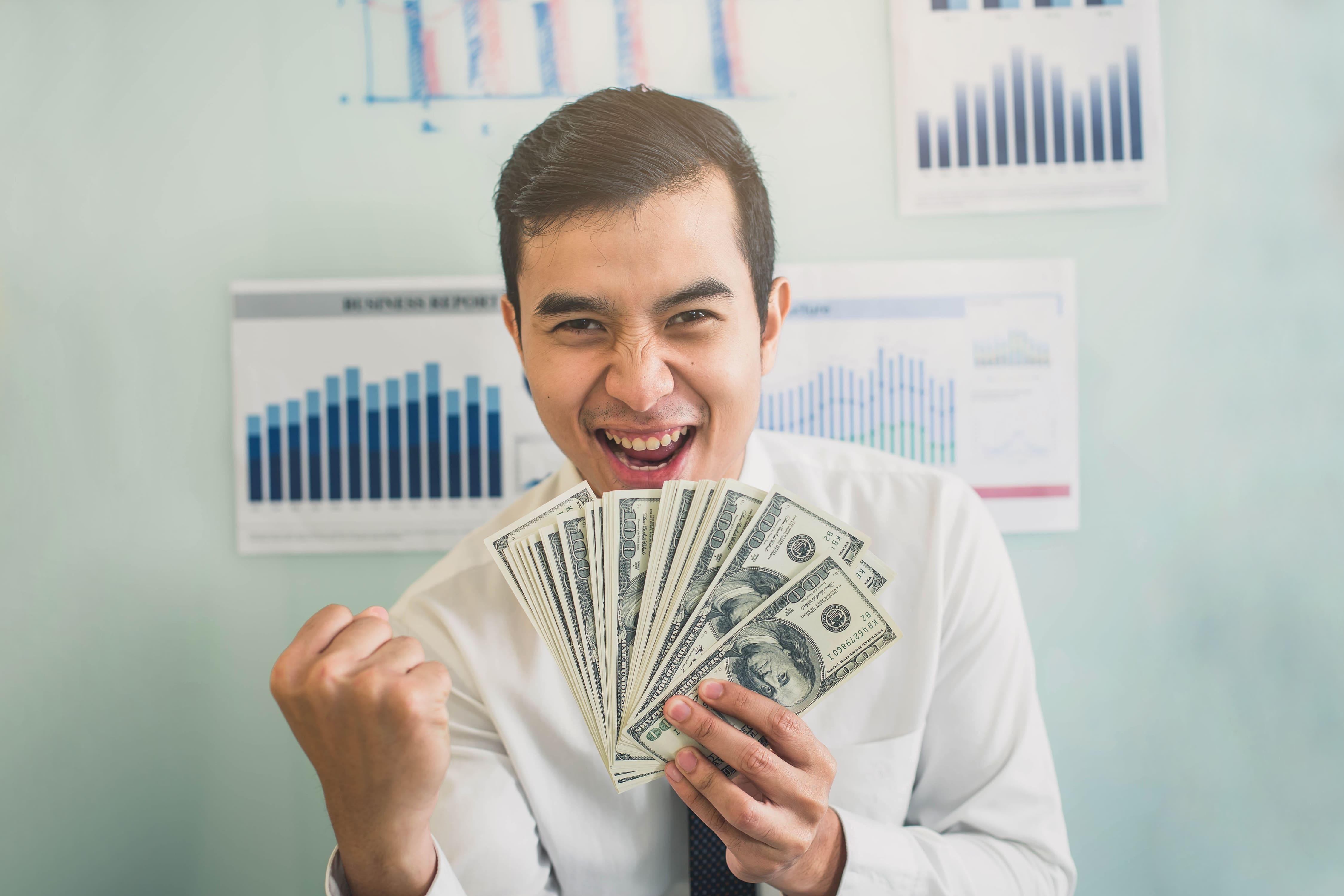 Imagem de um empreendedor com dinheiro para remeter a ele que deseja saber como estimar o faturamento mensal da sua empresa