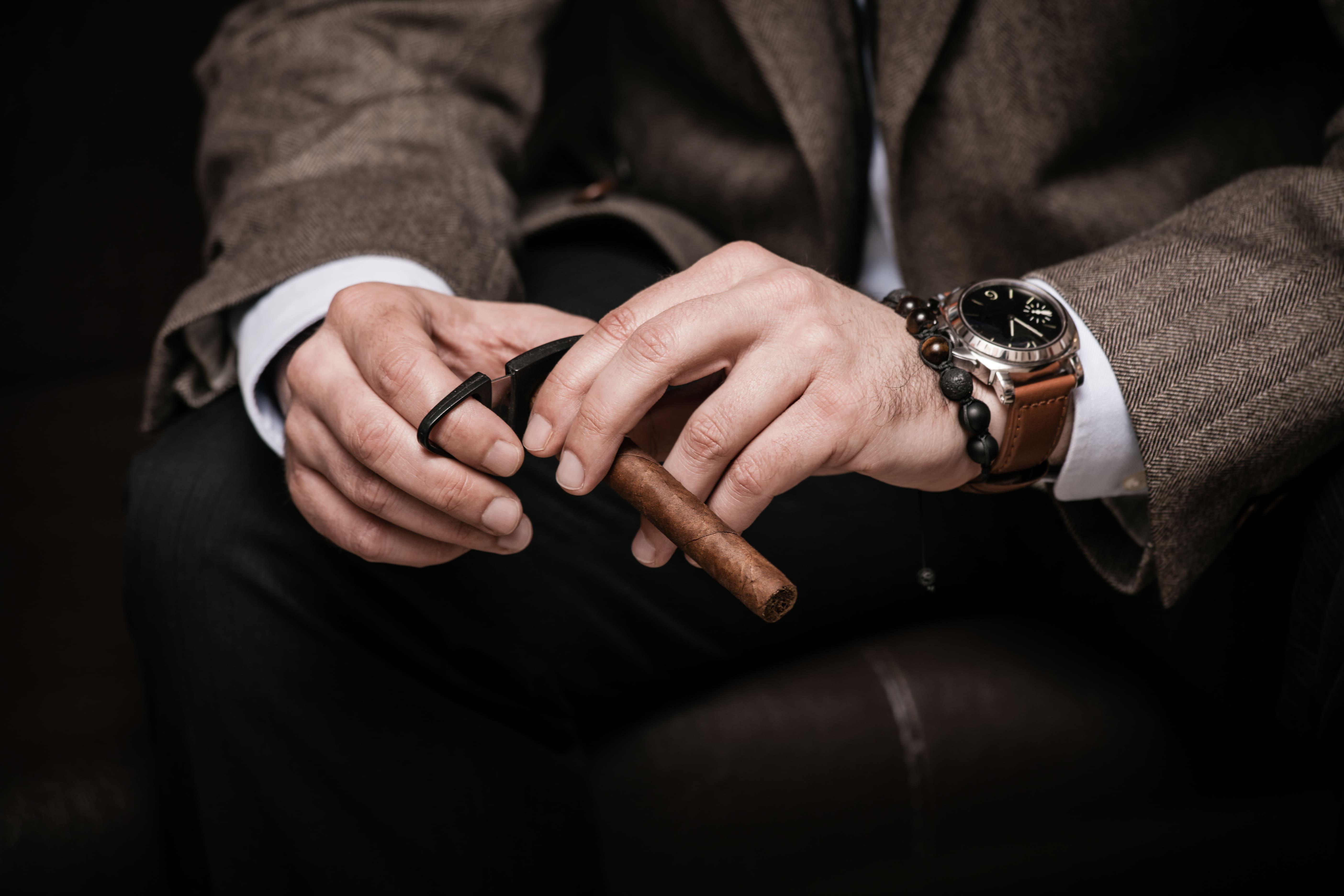 Imagem de um homem com um charuto na mão para remeter ao empreendedor que deseja abrir uma charutaria
