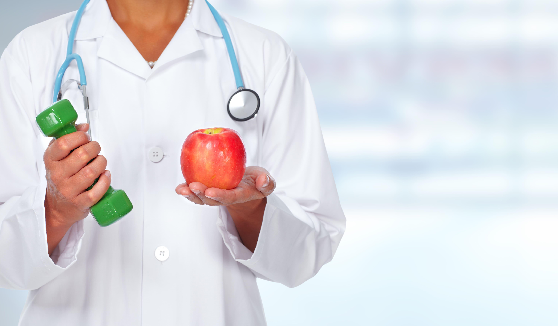Imagem de um médico segurando um peso e uma maçã para remeter ao empreendedor que deseja abrir uma clínica de saúde esportiva