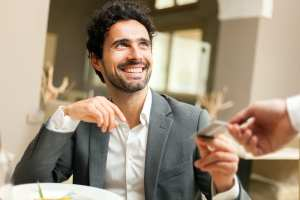 foto de um homem sorrindo e pegando um cartão de outra pessoa, representando o credmei