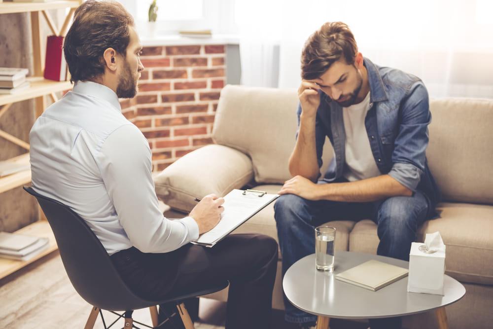 foto de um homem conversando com psicólogo, representando como abrir um consultório de psicologia