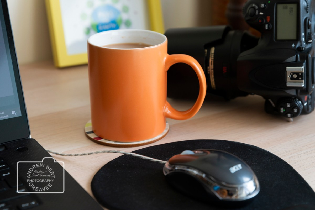 an orange mug of tea, a DSLR camera & a computer