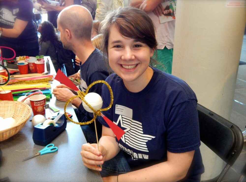 Abbie holding a craft model of a pulsar.