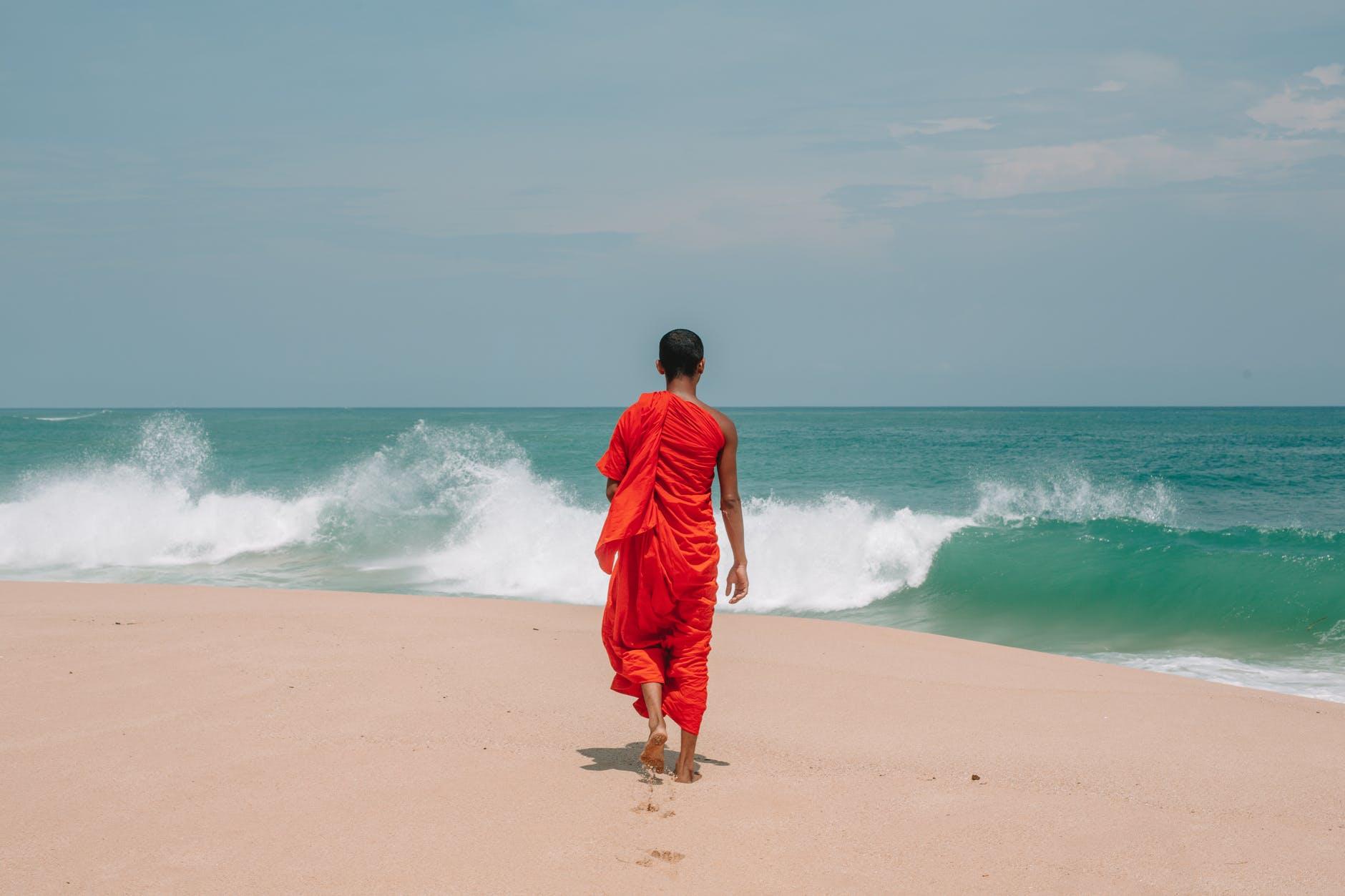 unrecognizable young ethnic man walking on seashore