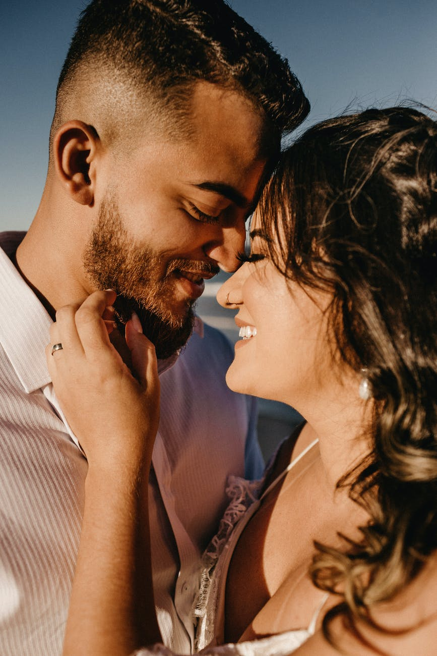 gentle young ethnic couple touching foreheads with closed eyes on sunny day
