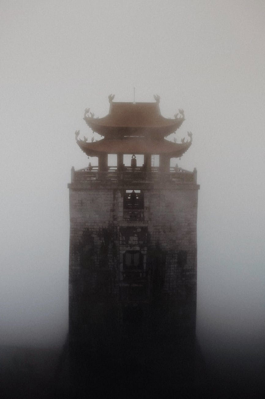 tall buddhist pagoda in dense fog