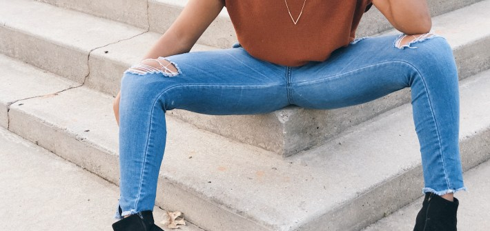 Picture of black booties, orange sweater and ripped skinny jeans