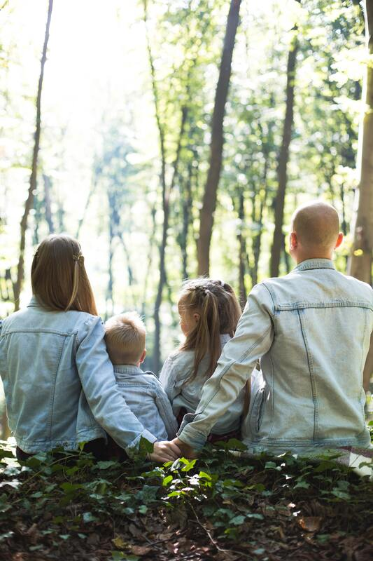 mom and dad holding hands with two kids sitting between them looking into a forest
