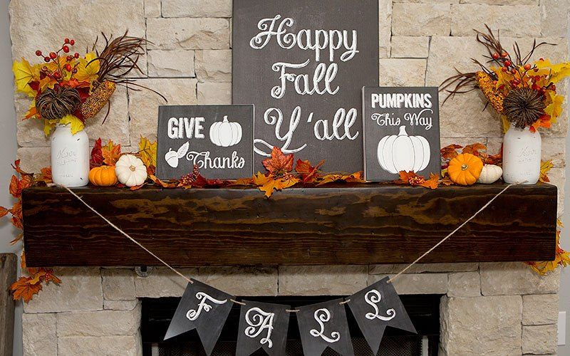 A beautiful and colorful fall mantel with chalkboard signs and fall foliage.