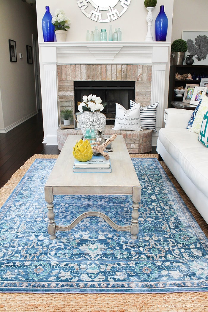 It's time for a change! Show some designer flare and learn how to layer rugs like a pro. The designers all do it for a reason. It makes BIG impact. Make your room pop with these 5 simple tips from A Blissful Nest. https://ablissfulnest.com/ #rugideas #designtips #homedecortips #livingroom #livingroomideas