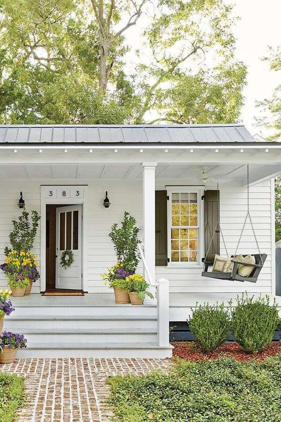 Love the pop of spring flowers on this front porch! #spring #springporch #springdecorating #springfrontporch