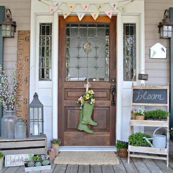 """Spring themed front porch with green rain boots hanging from the door with yellow, white and pink flowers planted. An old fashioned chalkboard sign has """"bloom"""" written on it, surrounded by small planted greenery. Grey metal lanterns and various floral accents surround the dark wood front door."""