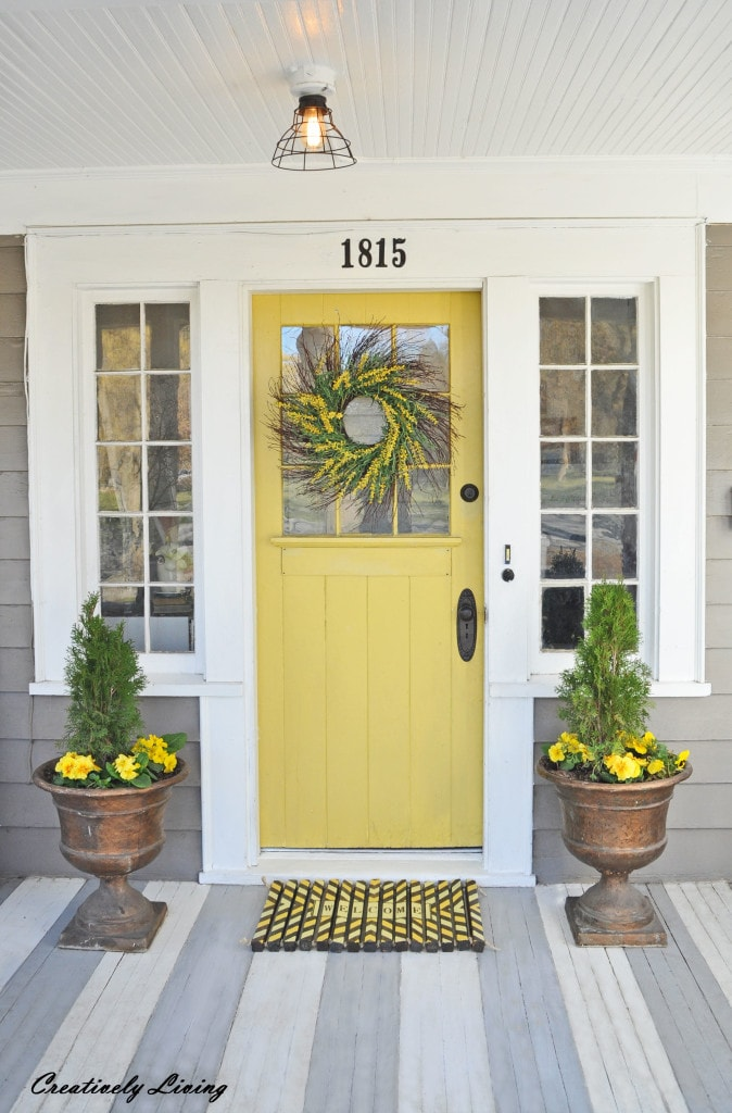 Love the bright sunny yellow color of this spring front porch door! #spring #springporch #springdecorating #springfrontporch