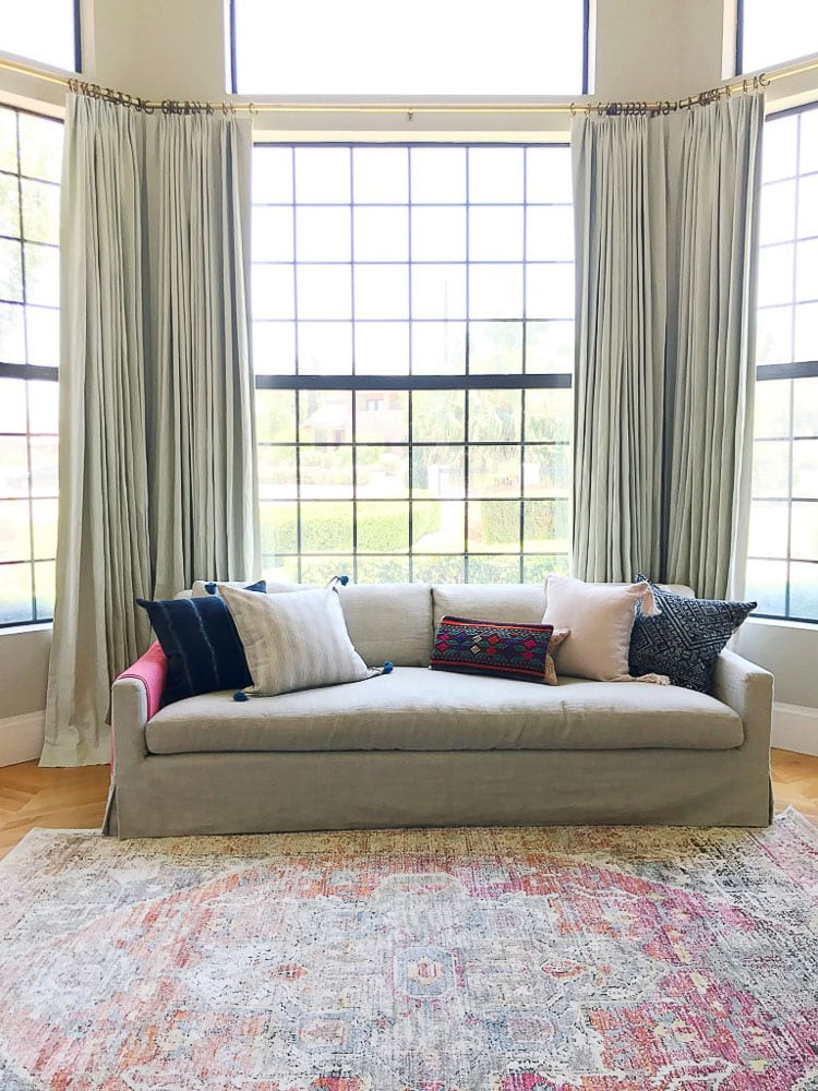 The five throw pillows on this soft couch leaves some open space on the couch, making the surface look welcoming and not overstuffed.