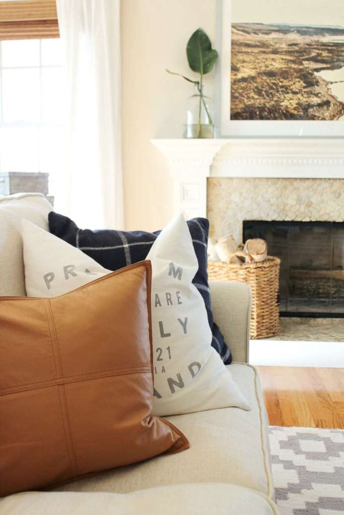 Two fabric pillows and one leather pillow on this couch gives a welcome change in texture in this living room scene