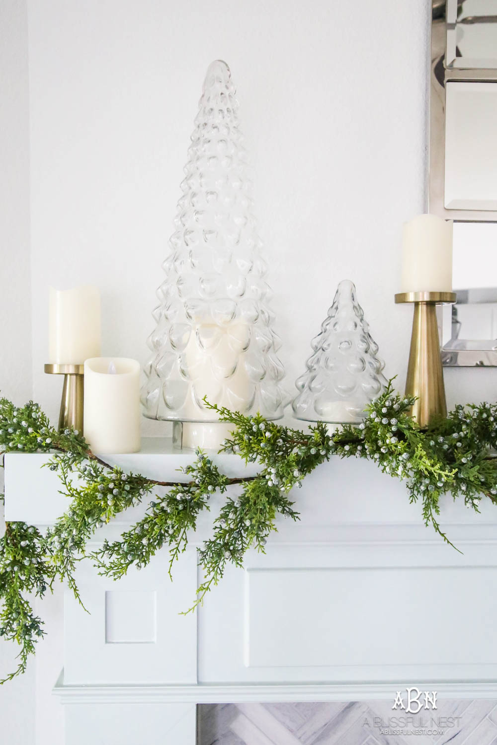 Gorgeous blue and silver Christmas mantle décor with juniper berry garland and glass hurricane Christmas trees. Simple and festive holiday décor in this open concept living space. Check out all the white, silver and gold Christmas decor in this holiday home tour on ABlissfulNest.com. #ABlissfulNest #Christmasdecor #Christmasdecorating #CoastalChristmasdecor #christmastree #christmasmantle