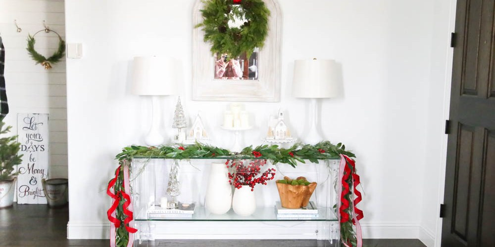 Dress up the entry with classic Christmas décor like a beautiful garland and red and white ribbon. Layered garland creates a fuller look. Add in berries to a vase. Create a festive holiday look in this narrow entryway space. #christmasentryway #christmasentry #christmasentrydecor #christmasentrywayideas #christmashometour