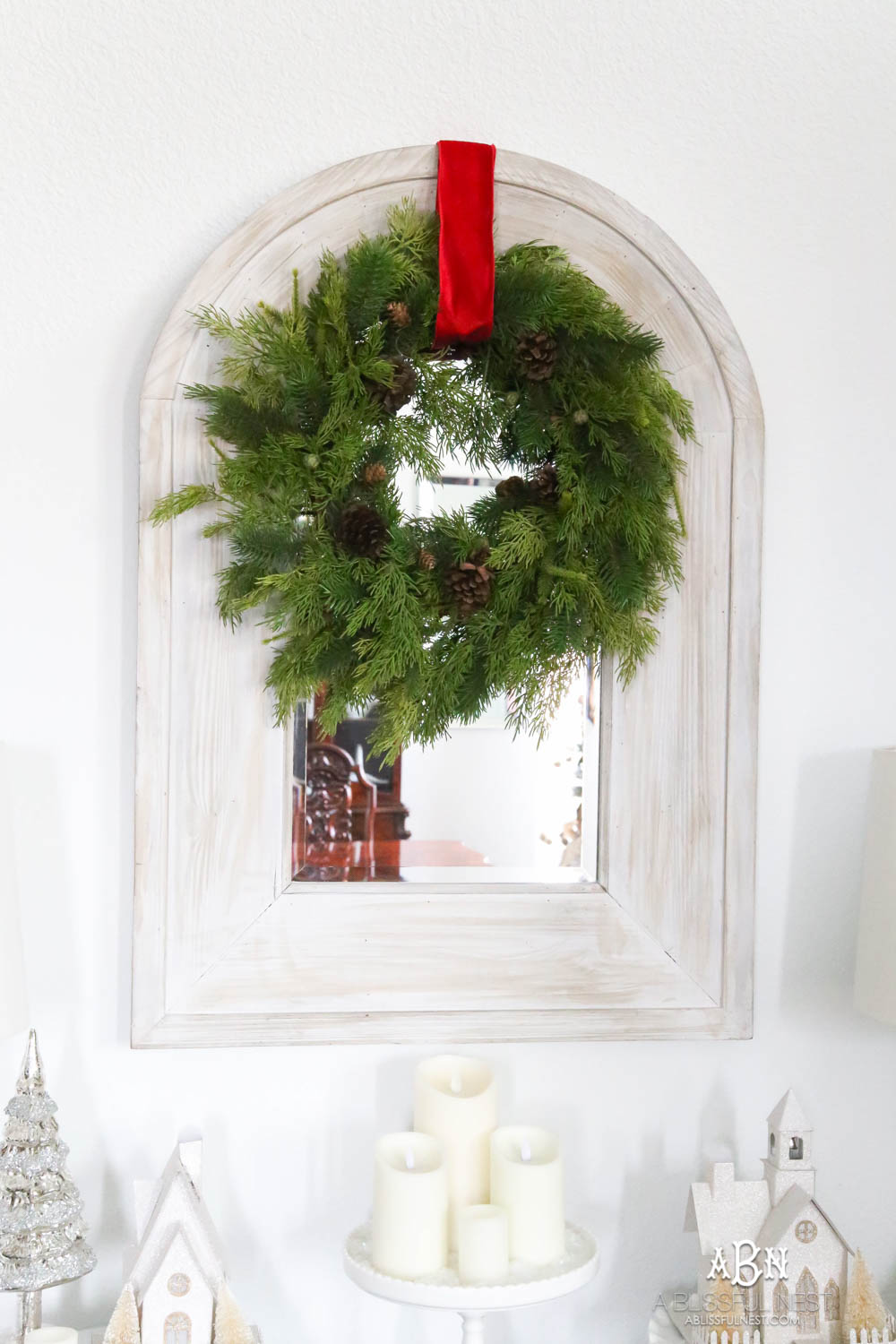 Simple classic Christmas wreath detail on a mirror in an entry. Simple holiday decor that makes a big impact. Red ribbon on a plain wreath. White walls in this holiday home which makes the décor really pop. #christmasentryway #christmasentry #christmasentrydecor #christmasentrywayideas #christmashometour