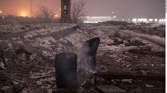 Um homem aquece a água em uma fogueira