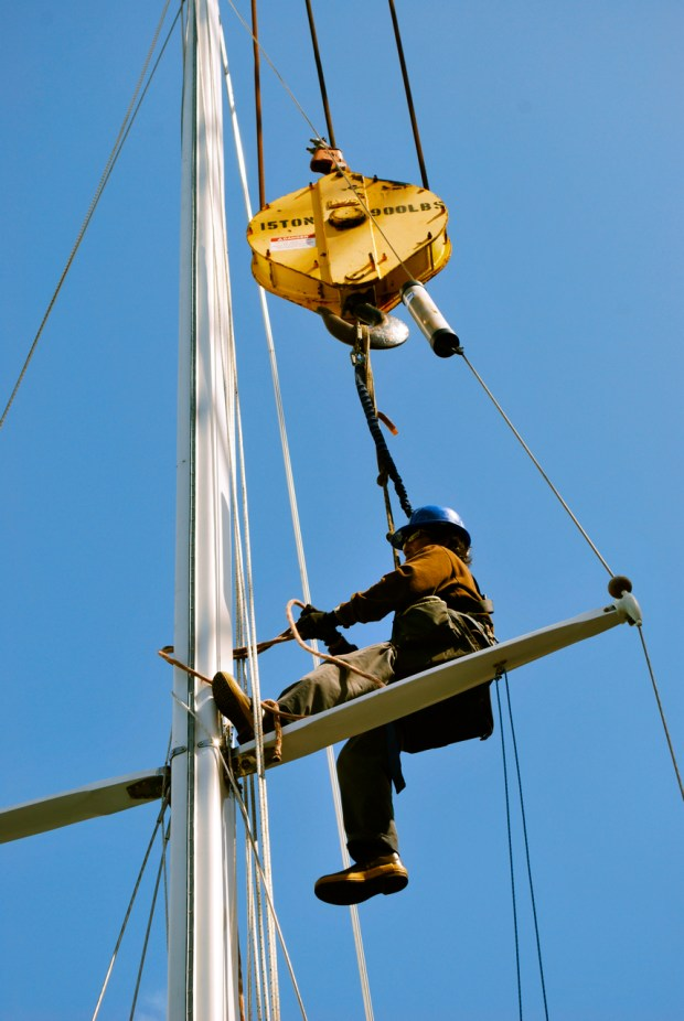 After all the stays are connected a yard worker get's hoisted up by the crane to remove the lines used to hoist the mast