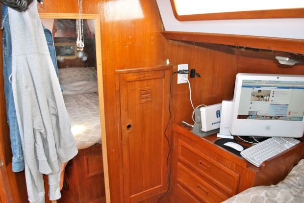 Looking forward in the master cabin showing the mirror, hanging locker, chartplotter and computer