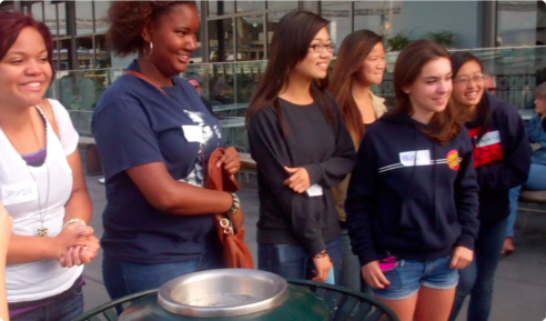 A group of racially diverse teen girls are standing in a group. They appear to be listening to something in front of them and smiling and laughing.