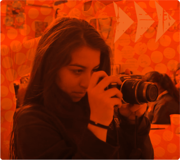 A teen girl with light skin and long dark hair is holding a large black camera. She is looking through the viewfinder with her hand on the shutter button. The image is overlaid by a bright orange filter.