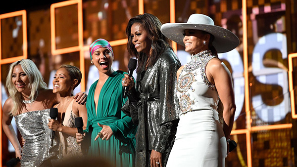 Alicia Keys, Jennifer Lopez, Michelle Obama, Lady Gaga, and Jada Pinkett Smith stand in a row smiling while Michelle holds the mic.