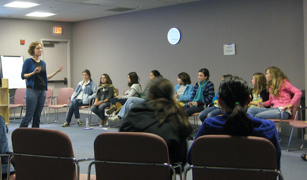 A group of 11 teen girls are seated in a circle, looking to the front of the room. A woman stands at the front, speaking to the group.