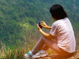 Girl reading an ebook on a hillside