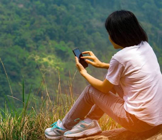 Girl reading an ebook on a hillside