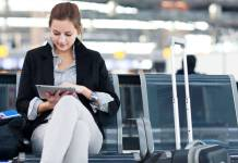 Woman in airport lounge reading on a tablet