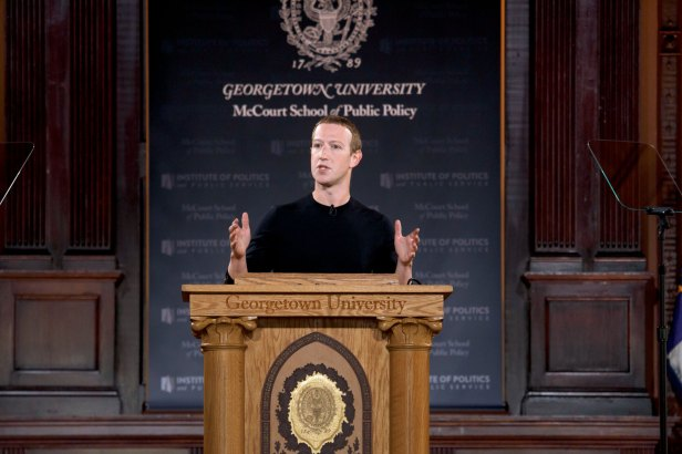 Mark Zuckerberg in black shirt onstage behind podium delivering speech