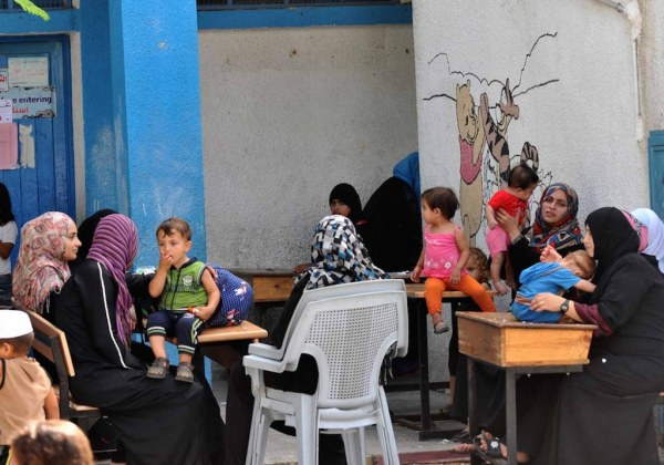 Palestinian families take shelter at an UNRWA school in Gaza City, after evacuating their homes in the northern Gaza Strip. Gaza City, July 13, 2014 © Shareef Sarhan/UNRWA Archives