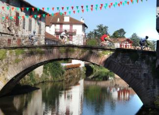 Cyclists crossing the picturesque bridge in the rural town of Saint Pied de Port in the Pyrenean foothills. Tourisme Béarn Pays Basque