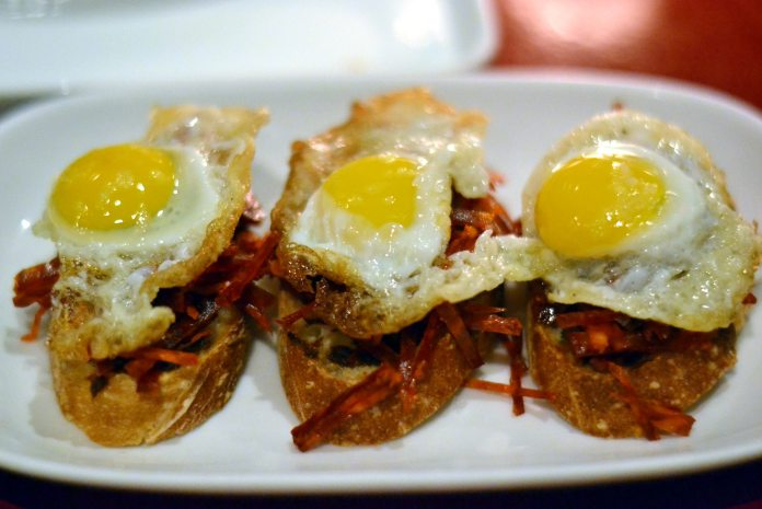 A pintxo of chorizo, sofrito, and egg. Txikito