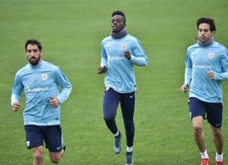 In this Tuesday Nov. 24, 2015 photo, Athletic Bilbao's Inaki Williams, center, warms up with Ander Iturraspe, and Raul Garcia, left, during a team training session in Lezama, near to Bilbao, northern Spain, Tuesday, Nov. 24, 2015. Inaki Williams is not the type of soccer player you would expect to see at Athletic Bilbao, the traditional Spanish club that only fields players from Bilbao and its neighboring Basque regions. (AP Photo/Alvaro Barrientos)