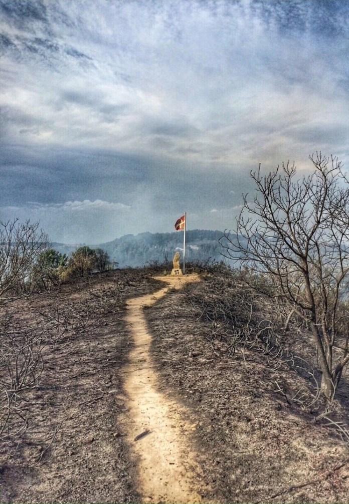 Una ikurrina ondea sobre los montes vascos tras sobrevivir a un incendio forestal que ha arrasado una amplia extension de monte de Berango y Sopela en Bizkaia
