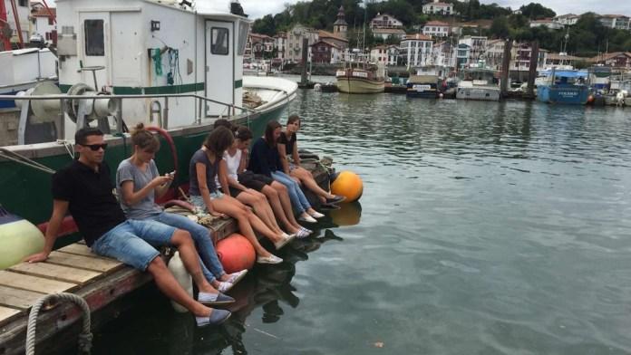 Espadrille-Parade im Hafen von St.-Jean-de-Luz. Zwei Jungunternehmerinnen umringt von Freunden. Alle lieben ihre Schuhkreationen.