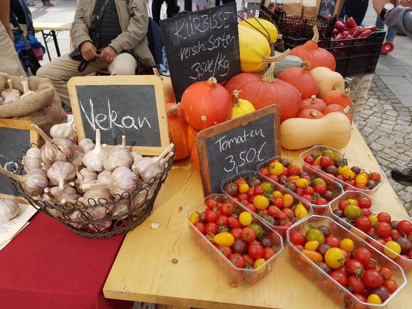 Marktstand mit Knoblauch, bunten Tomaten und Kürbissen